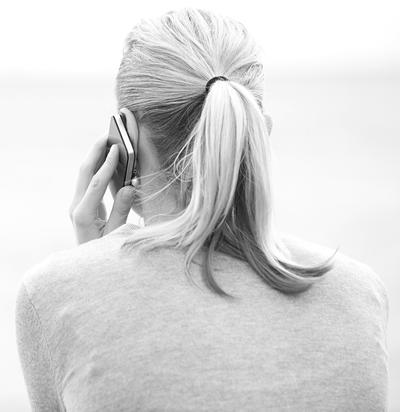Bild vergrößern: Rear view of a blonde woman with a ponytail chatting on a mobile phone facing out over the sea with copyspace
